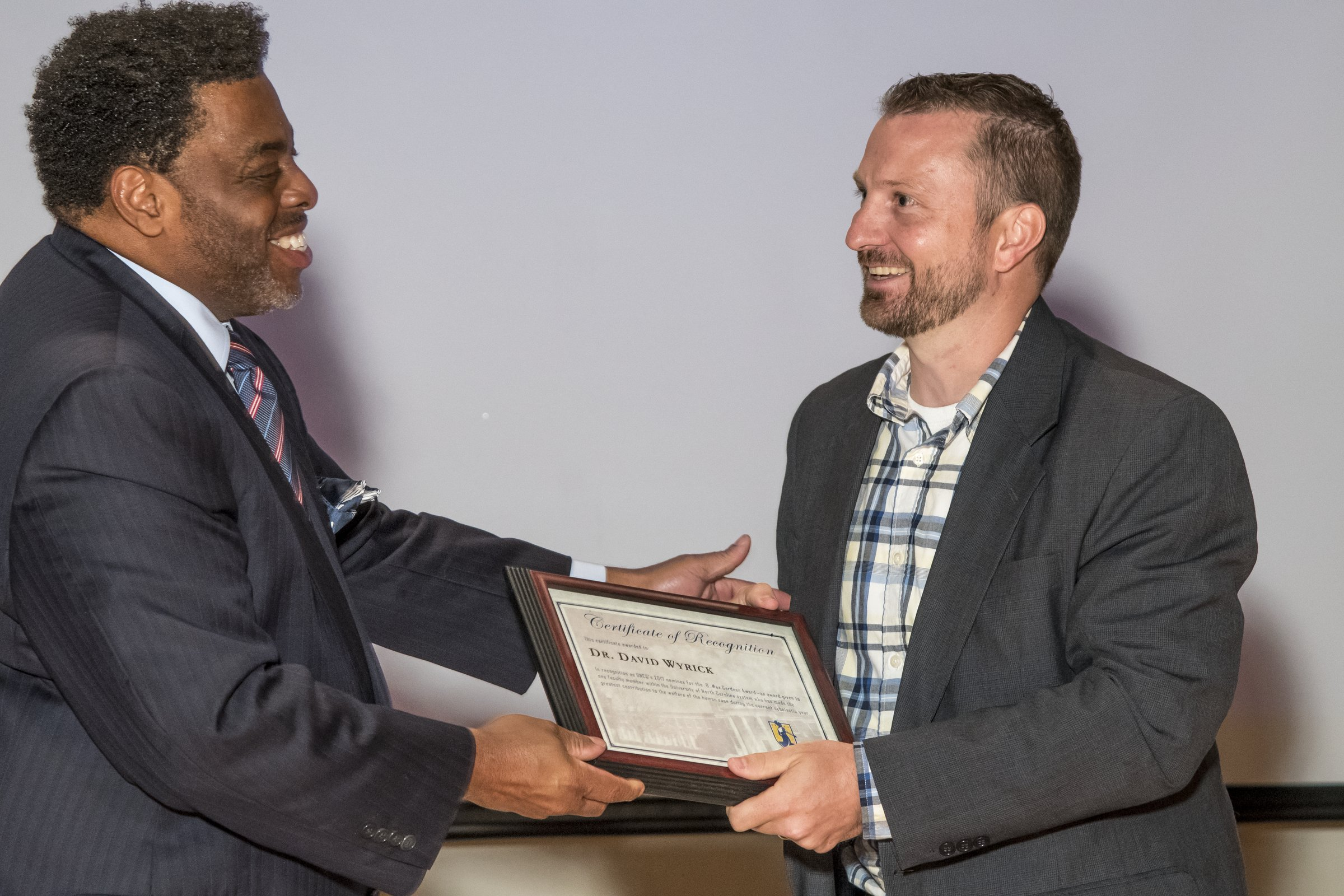 Photo of Chancellor Gilliam presenting an award to a male.