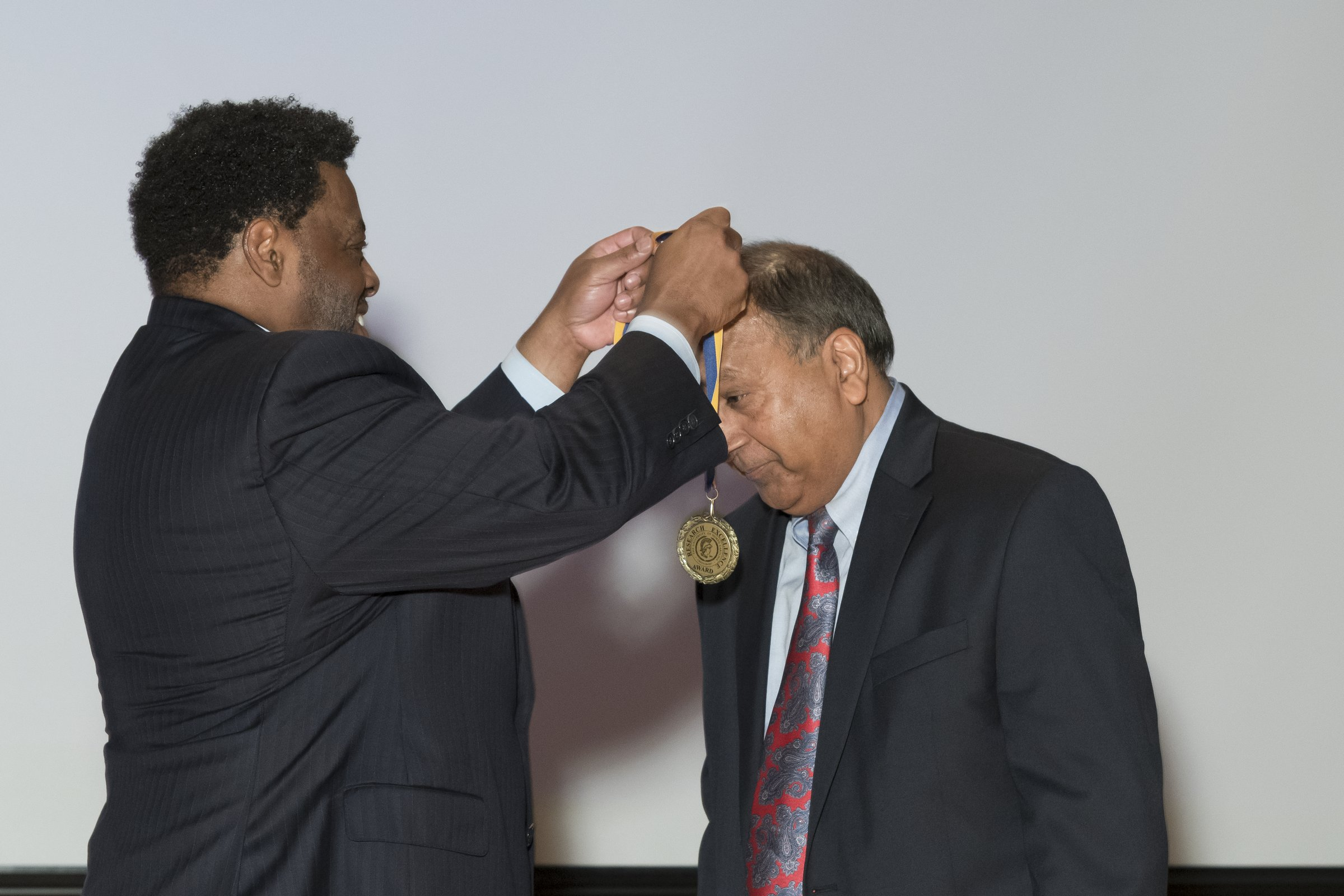 Photo of Chancellor Gilliam presenting an award to a male recipient