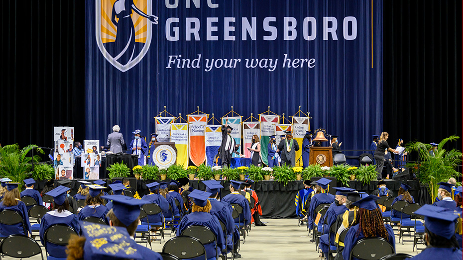 A Class of 2020 Commencement ceremony showing the stage in the background and socially-distanced graduates seated in the foreground